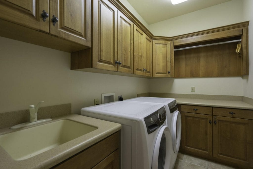 The laundry room has more than enough storage as well as a large sink!